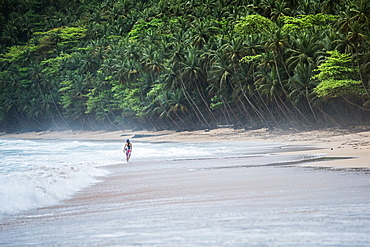 Young female surfer walking along the beach, Sao Tome, Sao Tome and Principe, Africa