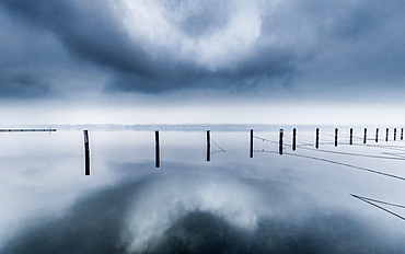 Reflecting UFO cloud over abandoned marina on a foggy winter morning at Lake Starnberg, Bavaria, Germany