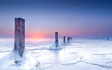 Icy winter morning in abandoned marina, wooden posts in the frozen lake at sunrise, Seeshaupt, Lake Starnberg, Bavaria, Germany