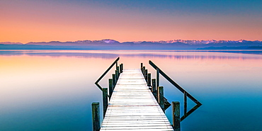 Winter morning with a snow-covered jetty at sunrise on Lake Starnberg, Bavaria, Germany