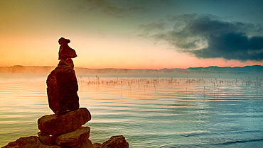 Stone men at sunrise on Lake Starnberg, Bernried, Bavaria, Germany