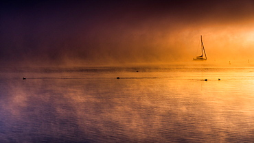 Foggy autumn mood at sunrise on Lake Starnberg, Bavaria, Germany