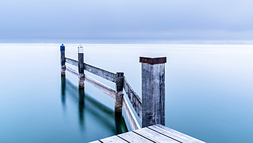 Snow-covered jetty in marina in winter on Lake Starnberg, Seeshaupt, Bavaria, Germany