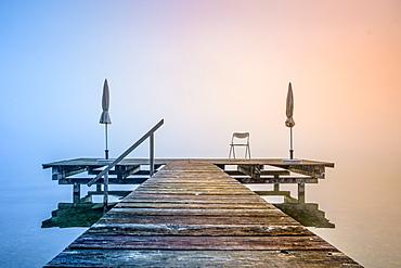 Jetty with folded parasols at misty sunrise on Lake Starnberg, Seeshaupt, Bavaria, Germany