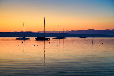 Boats in the backlight, at sunrise on Lake Starnberg, Tutzing, Bavaria, Germany