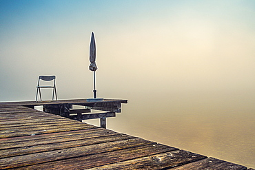 Jetty with folded parasols at misty sunrise on Lake Starnberg, Seeshaupt, Bavaria, Germany