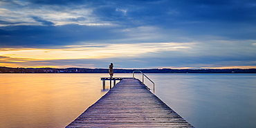 Woman on jetty at sunset on Lake Starnberg, St. Heinrich, Bavaria, Germany