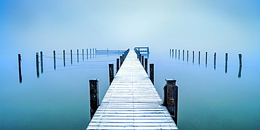 Snow-covered jetty in marina at misty sunrise on Lake Starnberg, Seeshaupt, Bavaria, Germany