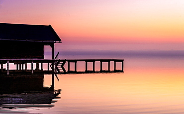 Boathouse silhouette at sunrise on Lake Starnberg, Bavaria, Germany