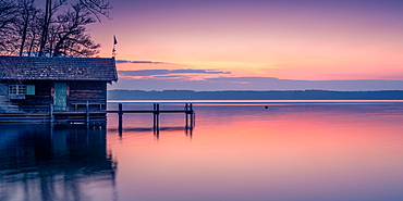 Boat hut and jetty at sunrise on Lake Starnberg, Bavaria, Germany