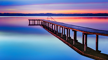 Jetty on Lake Starnberg at sunset with a view of the mountains, St. Heinrich, Bavaria, Germany