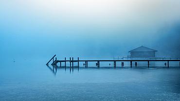 Boathouse with jetty in the fog on Lake Starnberg, Garatshausen, Bavaria, Germany
