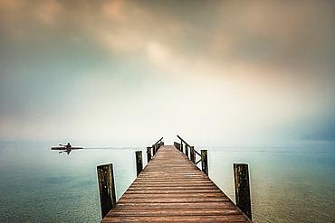 Jetty in the fog at Lake Starnberg, Garatshausen, Bavaria, Germany