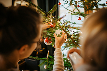 Mother decorates Christmas tree with her son, family, Christmas