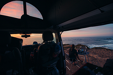 Woman sitting in front of her camper while having breakfast with the coast of Portugal in view, vacation, camping, Portugal
