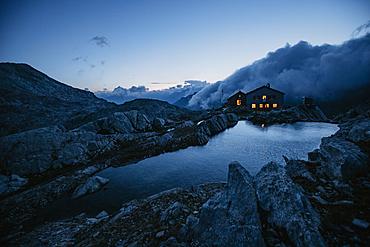 Illuminated mountain hut in the Swiss mountains, Switzerland, mountain range, mountain hut,