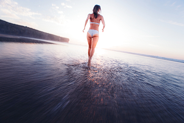 Woman running in bikni over the beach in the evening, Portugal, vacation
