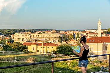 Female tourist with map at ancient Roman Amphitheatre known as Pula Arena, Pula, Istria, Croatia