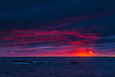 Clouds glowing a bright pink on the horizon over water, Bonavista, Newfoundland, Canada