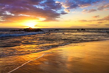 A golden sunset with reflection on sand at Ulua Beach, Wailea, Maui, Hawaii, United States of America