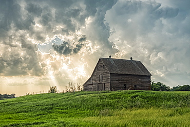 Abandoned barn with storm clouds converging overhead, Nebraska, United States of America