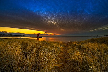 Herd Groyne Lighthouse and dramatic sunset with glowing clouds and beach grass in the foreground, South Shields, Tyne and Wear, England