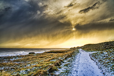 Snow-covered path along the coastline with golden sunlight illuminating the clouds, South Shields, Tyne and Wear, England