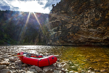 Packraft on the banks of the Charley River, sun going down behind ridge in background, Yukon-Charley Rivers National Preserve, Alaska, United States of America