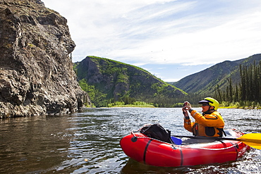 Woman photographing from her Packrafting on the Charley River in summertime, Yukon–Charley Rivers National Preserve, Alaska, United States of America