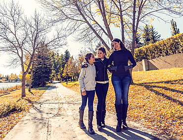 A mother and her two daughters walking and talking on a pathway in a city park on a warm autumn day, Edmonton, Alberta, Canada