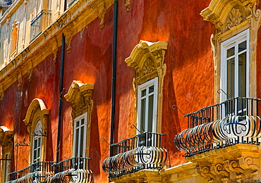 Facade of a residential building with ornate balconies and corbels, Syracuse, Sicily, Ortigia, Italy