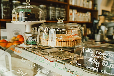 Display of confectioneries behind glass at a bakery, Italy