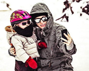 A Mother And Daughter Dressed In Winter Coats, Hats And Sunglasses Taking A Self-Portrait With A Smart Phone While Tobogganing on Vacation, Fairmont Hot Springs, British Columbia, Canada