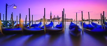 Gondolas moored along the shoreline of the Grand Canal during a vibrant sunset with a view of San Giorgio Maggiore and church in the distance, Venice, Italy