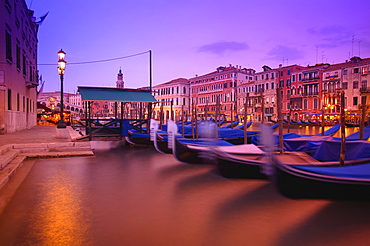 Gondolas moored along the shoreline of the Grand Canal during a vibrant sunset, Venice, Italy