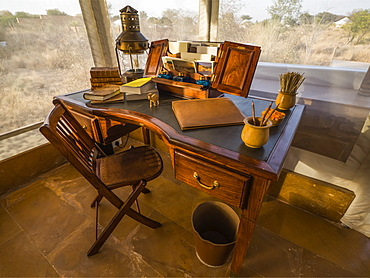 Desk in the foyer of a tent surrounded by windows with a view out to a landscape of dry brush and trees, Rajasthan, India