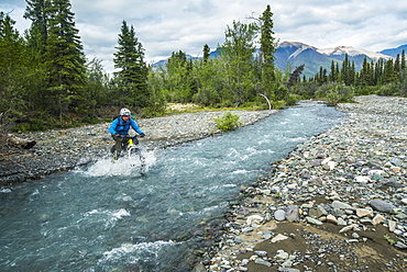 A man fat biking across a stream in Wrangell-St. Elias National Park and Preserve on a cloudy summer day in South-central Alaska, Alaska, United States of America