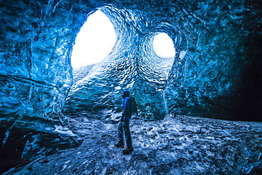 Person standing underneath the openings of a glacier, South Iceland, Iceland