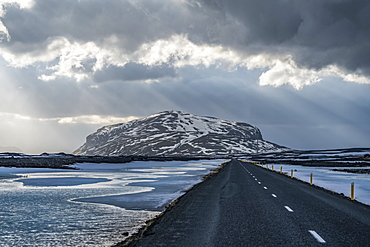 Road leading into the dramatic landscape of Iceland while the sun shines through the clouds making a beautiful scene, Iceland