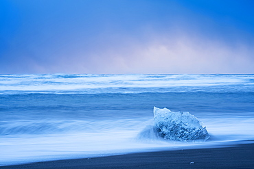Piece of ice being hit by waves along the South shore of Iceland with stormy skies behind it, Iceland