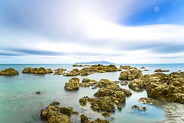 Rocks in the ocean along the shoreline in Pukerua Bay, Kapiti Island, Wellington, New Zealand