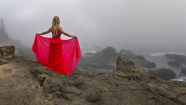 A woman stands on a cliff edge overlooking the angry sea on a foggy late afternoon in State Arago Park, stitched pano composite, Coos County, Oregon, United States of America