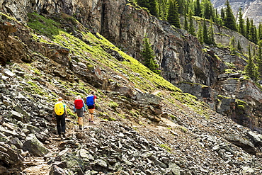 A group of female hikers along a rocky mountain pathway with rock cliffs in the background, British Columbia, Canada