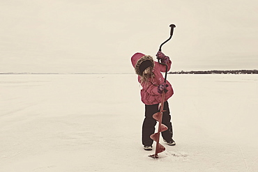Young Girl Trying To Drill A Hole In The Ice Of Frozen Lake Wabamun Without Any Success: Wabamun, Alberta, Canada