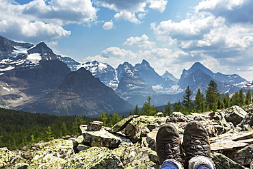 Hiker's boots resting on a rocks with valley and mountain range in the background, British Columbia, Canada