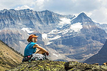 Female hiker sitting on a rocky area overlooking mountain vista in the background, British Columbia, Canada
