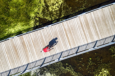 Aerial view looking straight down on a female cyclist on a bridge across a swampy pond with shadow of cyclist, East of Calgary, Alberta, Canada