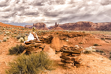 A woman sits on a rock in the Valley of the Gods, Utah, United States of America