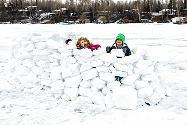 Children playing in a snow fort on frozen Lake Wabamun, Wabamun, Alberta, Canada