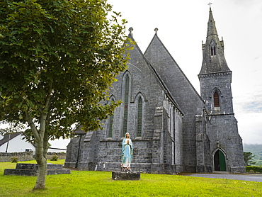 Stone church with bell tower and statue of praying woman in front, County Clare, Ireland